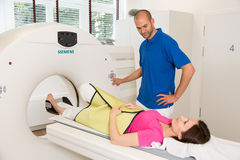Medical technical assistant preparing scan of the spine with CT Royalty Free Stock Images
