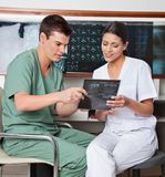 Medical Technicians Discussing About X-ray. Medical technicians having a discussion about x-ray at clinic Royalty Free Stock Photography