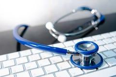 Medical technology. Stethoscope on white keyboard royalty free stock photography