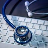 Medical technology. Stethoscope on white keyboard royalty free stock photo