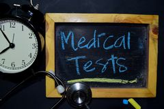 Medical Tests handwriting on chalkboard on top view. The words Medical Tests handwriting on chalkboard on top view. Alarm clock, stethoscope on black background stock image