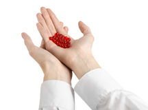 Medical theme: doctor's hand holding a red capsule for health on a white background isolated Royalty Free Stock Photos