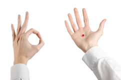 Medical theme: doctor's hand holding a red capsule for health on a white background isolated Royalty Free Stock Image