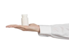 Medical theme: doctor's hand holding a white empty jar of pills on a white background Stock Images