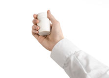 Medical theme: doctor's hand holding a white empty jar of pills on a white background Royalty Free Stock Image
