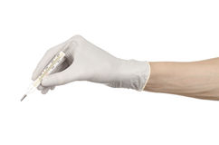 Medical theme: doctor's hand in white gloves holding a thermometer to measure the temperature of the patient on a white background Stock Photography