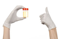 Medical theme: doctor's hand in white gloves holding a transparent container with the analysis of urine on a white background Royalty Free Stock Images