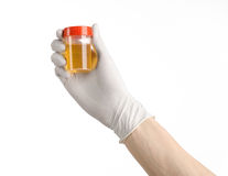 Medical theme: doctor's hand in white gloves holding a transparent container with the analysis of urine on a white background Royalty Free Stock Photos