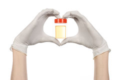 Medical theme: doctor's hand in white gloves holding a transparent container with the analysis of urine on a white background Stock Photos