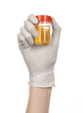 Medical theme: doctor's hand in white gloves holding a transparent container with the analysis of urine on a white background Stock Photo