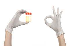 Medical theme: doctor's hand in white gloves holding a transparent container with the analysis of urine on a white background. Studio Stock Image