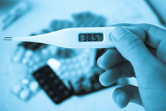 Medical thermometer and medicines in tablets Stock Image