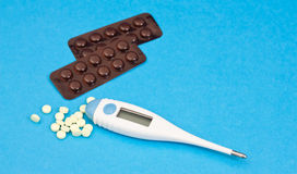 The medical thermometer and pills. Royalty Free Stock Image