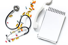 Medical things with notebook on white background top view composition with phonendoscope and pills call doctor mock up royalty free stock photo