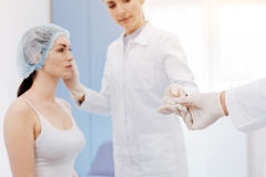Medical tool being given to a plastic surgeon. During the operation. Selective focus if a medical tool being given to a professional female plastic surgeon Royalty Free Stock Photos