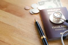 Medical tourism concept. Stethoscope with passport money and pen. On wooden table royalty free stock photography