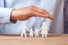 Medical or travel insurance. Man covers the family with his hands from his father, mother, son and daughter.  stock image