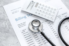 Medical treatmant billing statement with stethoscope and calculator on stone background. Medical treatmant billing statement with stethoscope and calculator on Royalty Free Stock Images