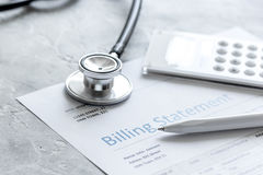 Medical treatmant billing statement with stethoscope and calculator on stone background. Medical treatmant billing statement with stethoscope and calculator on Stock Photo