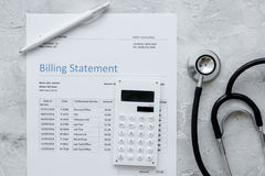 Medical treatmant billing statement with stethoscope and calculator on stone background top view. Medical treatmant billing statement with stethoscope and Stock Image