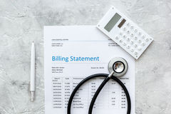 Medical treatmant billing statement with stethoscope and calculator on stone background top view. Medical treatmant billing statement with stethoscope and Royalty Free Stock Photography
