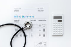 Medical treatmant billing statement with stethoscope and calculator on white background top view. Medical treatmant billing statement with stethoscope and Royalty Free Stock Photo