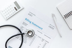 Medical treatmant billing statement with stethoscope and calculator on white background top view mock up Royalty Free Stock Images