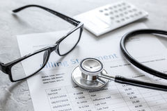 Medical treatmant billing statement with stethoscope and glasses on stone background Stock Photo