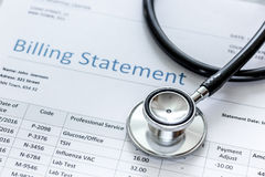 Medical treatmant billing statement with stethoscope on stone background. Medical treatmant billing statement with stethoscope on stone desk background Stock Image