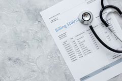 Medical treatmant billing statement with stethoscope on stone background top view mockup. Medical treatmant billing statement with stethoscope on stone desk Stock Images