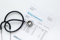 Medical treatmant billing statement with stethoscope on white background top view. Medical treatmant billing statement with stethoscope on white desk background Royalty Free Stock Photo