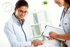 Medical treatment. Portrait of confident female doctors during medical treatment of patient in hospital royalty free stock image