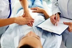 Medical treatment. Close-up of two doctors during medical treatment of patient in hospital royalty free stock photography