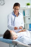 Medical treatment. Portrait of confident female doctor looking at patient during medical treatment in hospital stock images