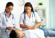Medical treatment. Portrait of confident female doctors during medical treatment of patient in hospital royalty free stock images