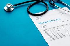 Medical treatment bill and phonendoscope on blue background. Medical treatment bill and phonendoscope on blue desk background royalty free stock photo