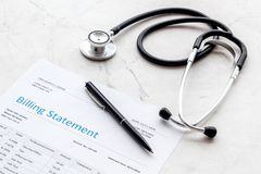 Medical treatment bill and phonendoscope on white background. Medical treatment bill and phonendoscope on white desk background royalty free stock photography