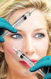 Medical treatment. Face of a beautiful woman with doctors hands and syringes Royalty Free Stock Photography