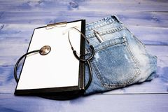 Medical treatment. Medicine concept. Medical help and consultation. Doctors attributes. Medical insurance. Phonendoscope. And paper tablet on jeans background royalty free stock photos