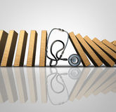 Medical Treatment. Symbol as a hospital doctor stethoscope stopping domino pieces from falling further as a metaphor for treating a patient with proper Royalty Free Stock Image