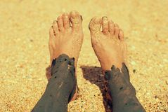 Medical treatments with mud on the sand by sea. Feet Royalty Free Stock Image