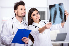 Medical. Two young doctors are looking at X-ray in medical office Stock Image