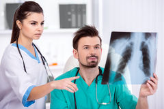 Medical. Two young doctors are looking at X-ray in medical office. Back view Royalty Free Stock Image