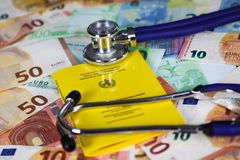 Medical vaccination cost concept - Stethoscope and yellow international certificate of vaccination on Euro paper money bank notes stock photography