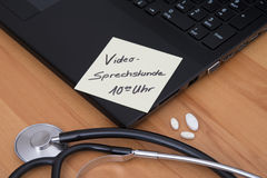 A medical video conference. A laptop with a stethoscope and a notepad with an appointment for a video conference between the doctor and the patient Royalty Free Stock Photo