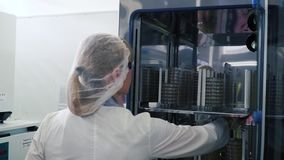 Medical Virology Research Scientist Works with Mask. Clip. Scientist Takes out Test Tubes from Refrigerator. She Works. In a Research Facility stock video