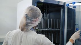 Medical Virology Research Scientist Works with Mask. Clip. Scientist Takes out Test Tubes from Refrigerator. She Works. In a Research Facility Stock Photos