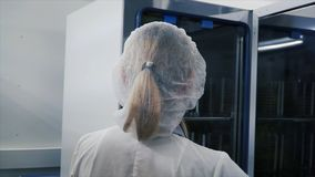 Medical Virology Research Scientist Works with Mask. Clip. Scientist Takes out Test Tubes from Refrigerator. She Works. In a Research Facility Royalty Free Stock Photo
