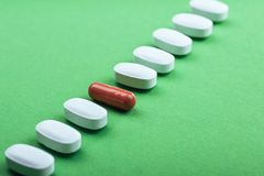 Medical white pills and brown capsules for the treatment and health care on a green background.  royalty free stock photography