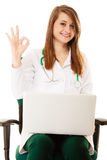 Medical. Woman doctor working on computer laptop. Medicine. Woman doctor in lab coat working on computer laptop showing okay hand gesture isolated Stock Photography